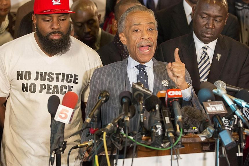 American civil rights leader, Rev. Al Sharpton (centre), speaks during a press conference at Greater St. Marks Church as Michael Brown Sr. (left) and Brown family attorney Benjamin Crump look on Nov 25, 2014 in Dellwood, Missouri, as Ferguson police