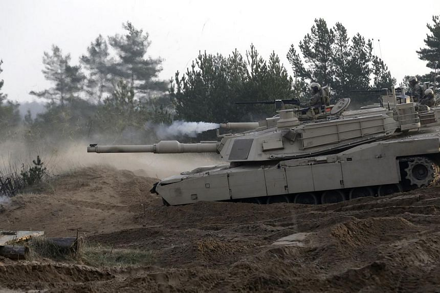 Members of the U.S. Army 1st Cavalry Division 1st Brigade Combat team deployed in Latvia on M1 Abrams tanks attend a military exercise in Adazi Nov 6, 2014. -- PHOTO: REUTERS