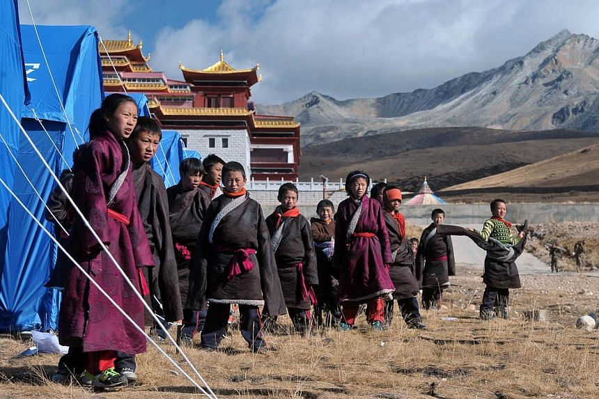 Youngsters gathering outside makeshift tents at a relief centre in Kangding on Nov 23, 2014 after a quake struck 39km north-west of Kangding on Nov 22. -- PHOTO: AFP