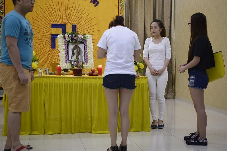 Ana Dina (second from right), 20, the younger sister of the late Tran Cam Ny, a 32-year-old Vietnamese woman who was murdered in an Ang Mo Kio flat on Nov 20, 2014, at her wake with other visitors on Nov 26, 2014. -- ST PHOTO: MARK CHEONG