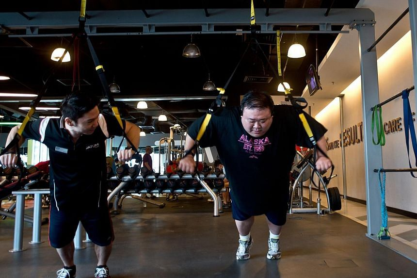 In this picture taken on Sept 12, 2014, 40-year old Malaysian civil engineer Kevin Lim (right) works out at a fitness centre in Kuala Lumpur. Bad eating habits and unhealthy lifestyles have helped Malaysia earn the not-so-flattering monicker as South