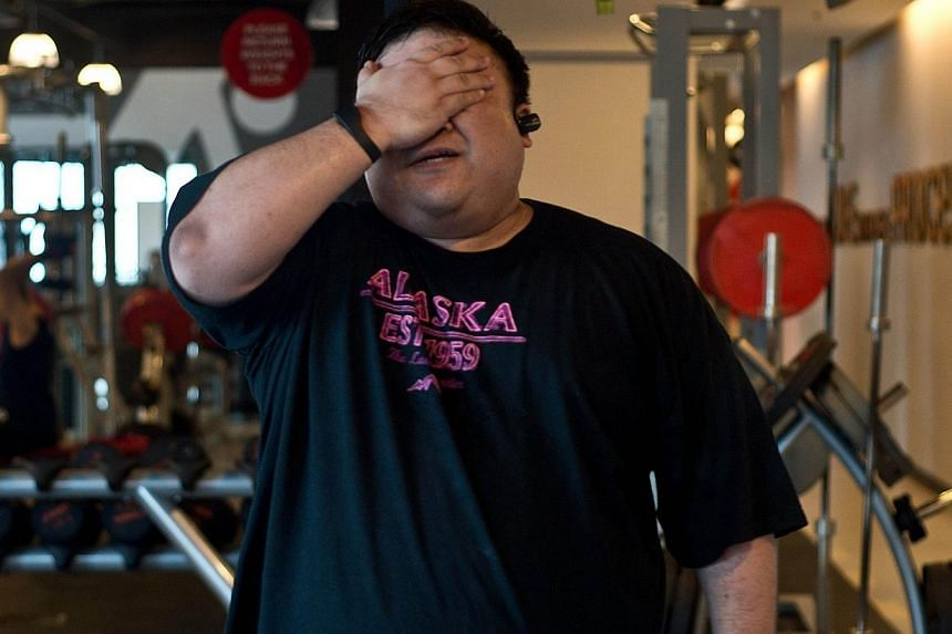 In this picture taken on Sept 12, 2014, 40-year old Malaysian civil engineer Kevin Lim gestures during a work-out session at a fitness centre in Kuala Lumpur. Bad eating habits and unhealthy lifestyles have helped Malaysia earn the not-so-flattering