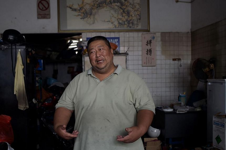 In this picture taken on Sept 8, 2014, Wong Siew Hong, a diabetic and automotive mechanic gestures while talking about his weight at his garage in Kuala Lumpur. Bad eating habits and unhealthy lifestyles have helped Malaysia earn the not-so-flatterin