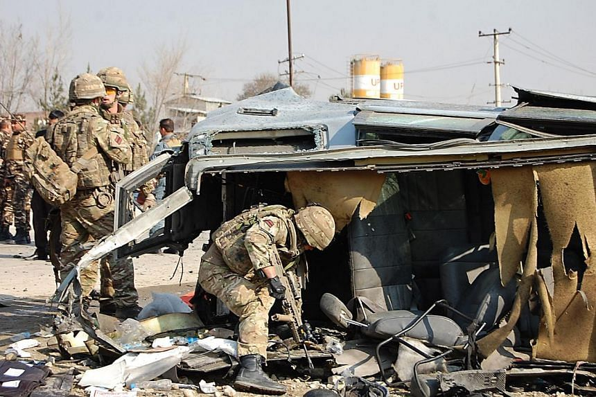 A NATO-led International Security Assistance Force (ISAF) soldier inspects a British embassy vehicle which was targeted in a suicide attack along the Kabul-Jalalabad road in Kabul on Nov 27, 2014. Britain said two people working for its embassy