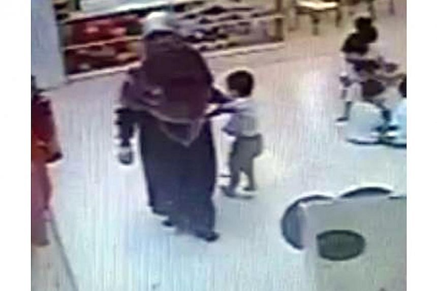 Screenshot of footage from a security camera at NTUC My First Skool in Toa Payoh, which captured childcare teacher,Siti Hadijah Mohamed Sin (left)grabbing a child by the arm when he ran towards her, before forcing him to sit. -- PHOTO: ST