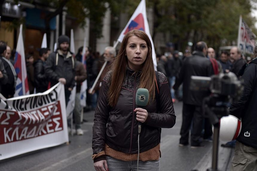 A foreign journalist reports on a media strike during a rally outside the journalists union in central Athens on Nov 26, 2014. Greek journalists went on a 24-hour strike shutting radio and TV broadcasts ahead of the general strike on Nov 27th. -- PHO
