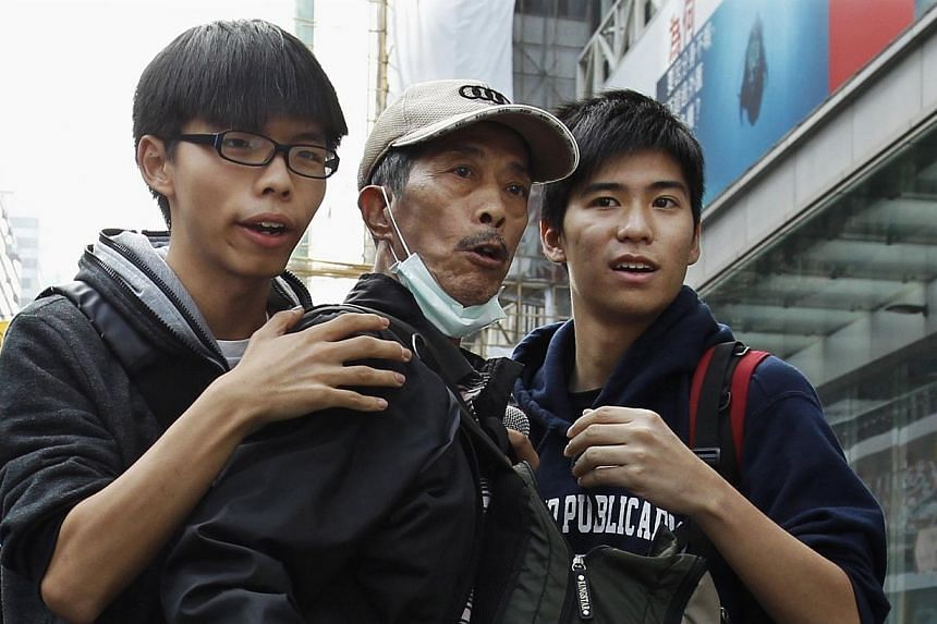 Student leaders Joshua Wong (left) and Lester Shum (right) hold back a protester behind a barricade while watching police movement at Mongkok shopping district in Hong Kong on Nov 26, 2014. -- PHOTO: REUTERS