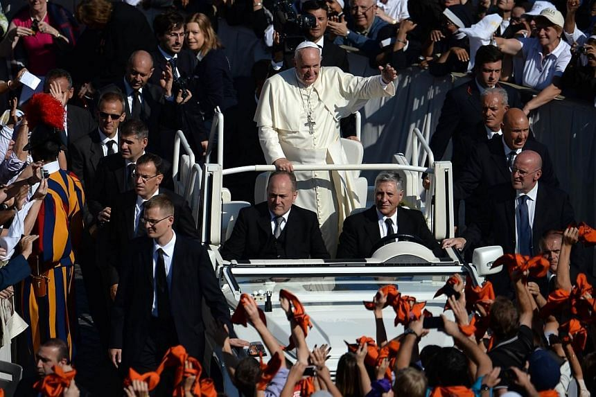 Pope Francis greets the crowd from the popemobile after a papal mass for the beatification of Paul VI, who died in 1978, and the end of Vatican's synod on the family at St Peter's square on Oct 19, 2014 at the Vatican.The Philippines will custo