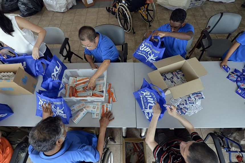 Volunteers from public health-care group SingHealth, as well as beneficiaries from the SPD (formerly the Society for the Physically Disabled), preparing race packs for The Straits Times Run at the Hub. -- PHOTO: ST FILE