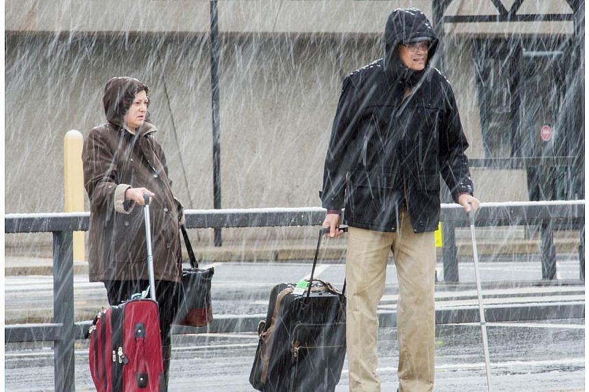 Airline passengers at Dulles International Airport outside Washington, DC, in Virginia, arrive to snow showers on the busiest travel day of the year on Nov 26, 2014. -- PHOTO: AFP
