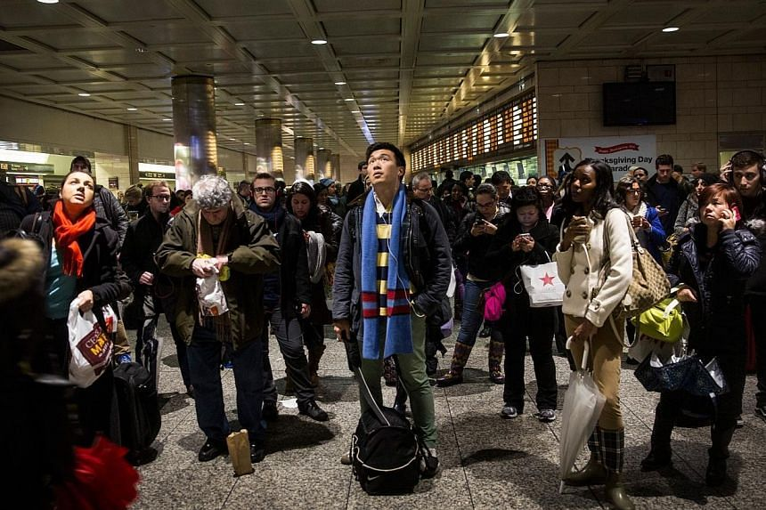 People wait for train information at New York Penn Station during rush hour on the night before Thanksgiving on Nov 26, 2014 in New York City.-- PHOTO: AFP