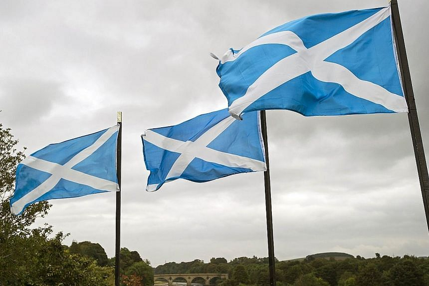A file picture taken on Sept 16, 2014, shows Scottish Saltire flags flying above the River Tweed in the town of Coldstream on the border between England and Scotland. -- PHOTO: AFP