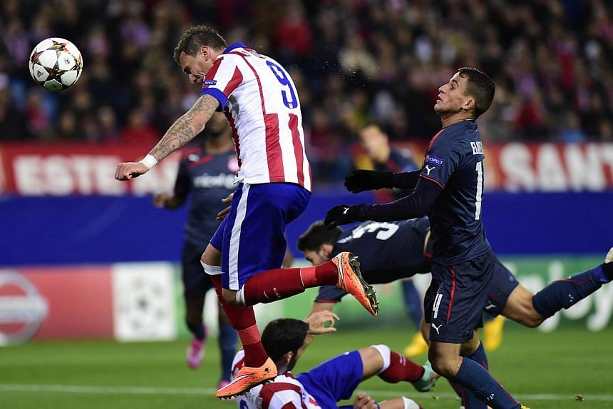 Atletico Madrid's Croatian forward Mario Mandzukic (left) heads the ball to score during the UEFA Champions League Group A football match against Olympiakos FC at the Vicente Calderon stadium in Madrid on Nov 26, 2014. -- PHOTO: AFP