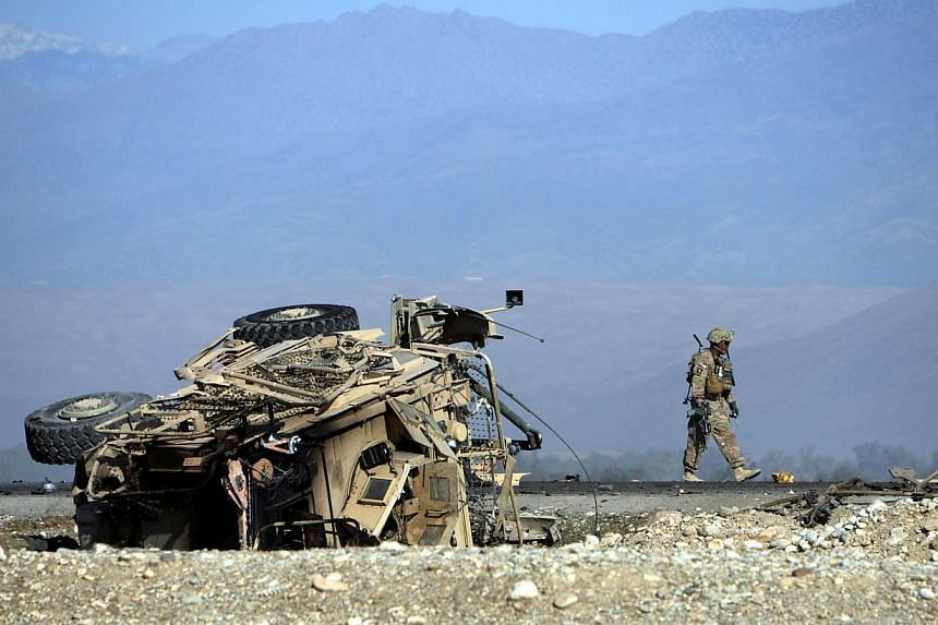 A US soldiers inspects the site of a suicide attack targeting foreign troops in Jalalabad on Nov 13, 2014. Afghanistan's upper house of parliament on Thursday approved two agreements with the US and NATO allowing about 12,500 troops to remain in the