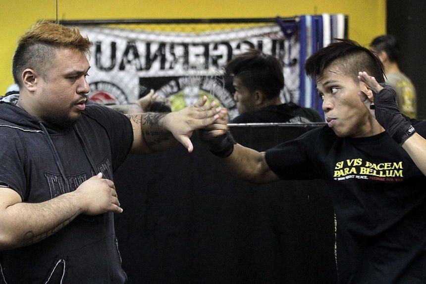 Singapore boxer Shahril Salim (right) training with coach Arvind Lalwani (left) at Juggernaut Fight Club on Oct 20, 2012. -- PHOTO: ST FILE