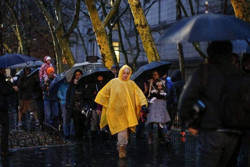 People carry umbrellas as they walk down the rain next to Central Park on Nov 26, 2014 in New York.More than 9,000 flights were cancelled or delayed in the US northeast as a winter storm snarled travel for Americans eager to celebrate Thursday'