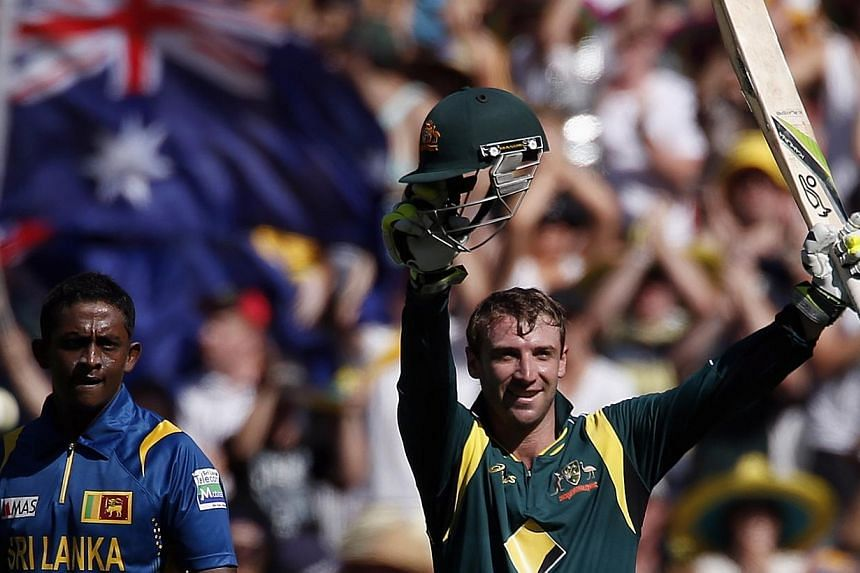 Australia's Phil Hughes celebrates reaching his century as Sri Lanka's Jeevan Mendis (left) looks on during the one-day international cricket match at the Melbourne Cricket Ground Jan 11, 2013. -- PHOTO: REUTERS