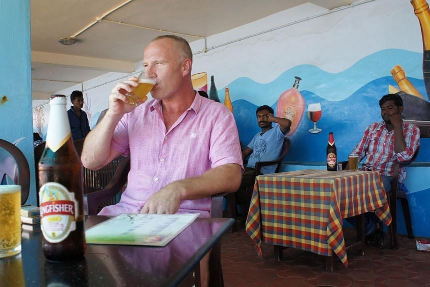 British tourist John Packer, a 41-year-old tiler, drinks a beer at a seafront restaurant in the resort town of Kovalam, in southern Kerala state on Sept 9, 2014.Tourists travelling to India from 43 countries including the US will no longer have