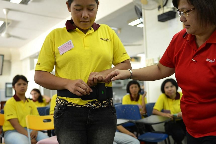 Madam Woon Siew Lan (right), a trainer at Nation Employment Maid Agency, teaching Miss Srilianti BR Sembiring, a domestic worker from Indonesia, on the usage of a fall detector device common in eldercare.Indonesiahopes to work with Singap