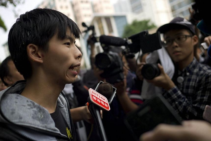 Student leader Joshua Wong (left) speaks with reporters after he was hit with an egg near a courthouse following his release on bail in Hong Kong on Nov 27, 2014.-- PHOTO: AFP