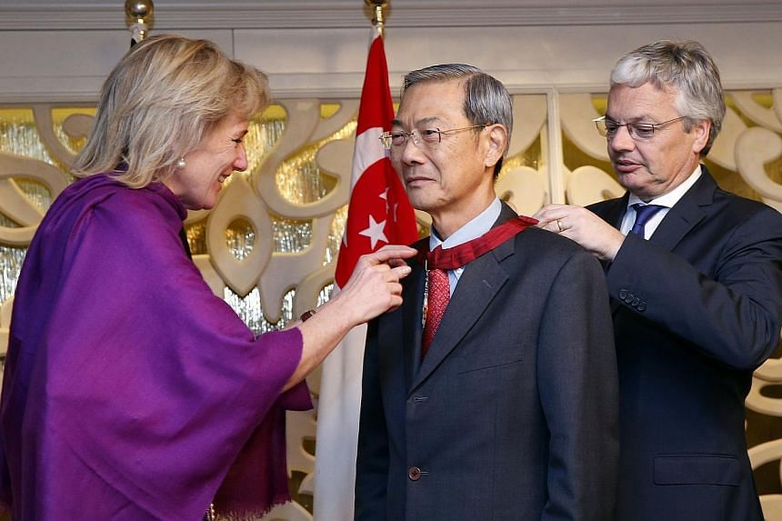 Lee Boon Yang, Chairman of Keppel Corporation (centre), receiving a medal from Belgium's Princess Astrid (left) with the help of Didier Reynders, Deputy Prime Minister and Minister of Foreign Affairs and European Affairs (right) of Belgium on Thursda
