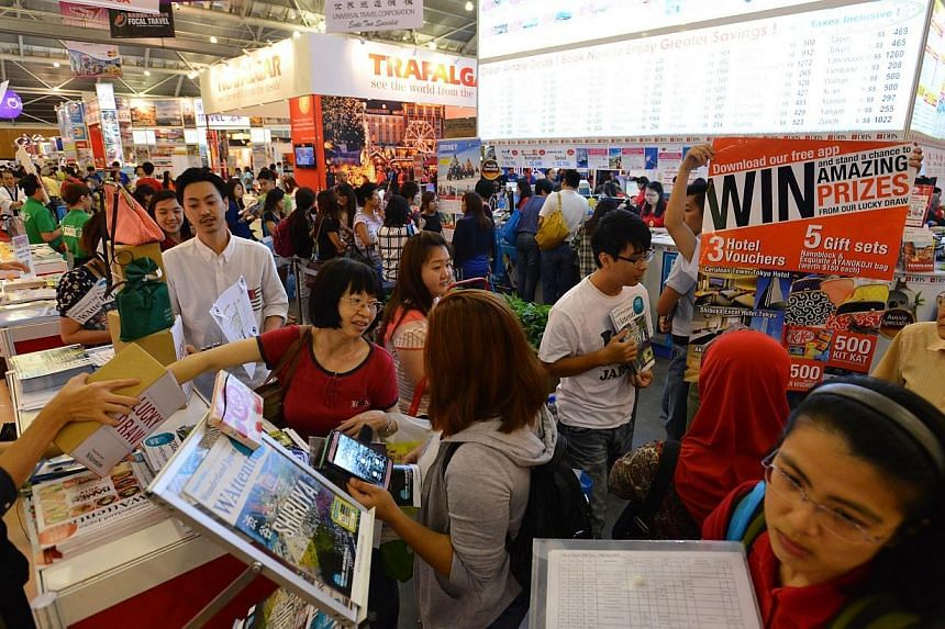 People at the Natas Holidays travel fair held in August 2014 at the Singapore Expo.Natas said on Thursday that it will waive the entrance frees to next year's fair, in line with Singapore's 50th birthday. -- PHOTO: ST FILE