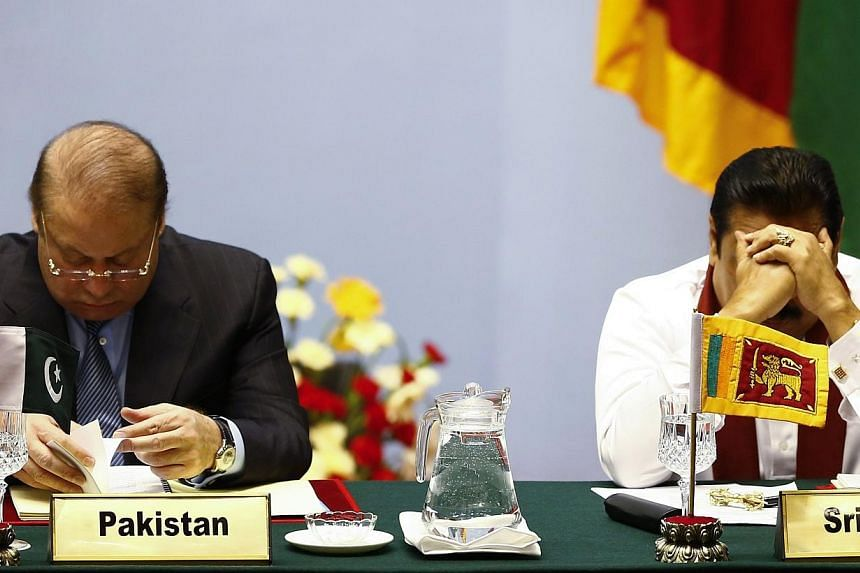 Pakistan's Prime Minister Nawaz Sharif (left) and Sri Lanka's President Mahinda Rajapaksa attend the opening session of 18th South Asian Association for Regional Cooperation (SAARC) summit in Kathmandu on Nov 26, 2014. -- PHOTO: REUTERS
