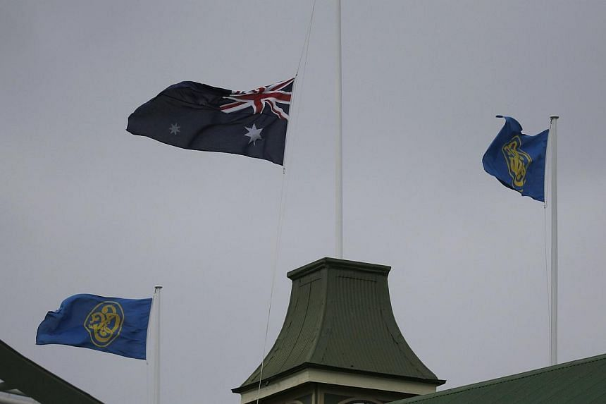 The Australian flag (centre) flies at half mast at the Sydney Cricket Ground following the announcement of the death of Australian cricketer Phillip Hughes in Sydney on Nov 27, 2014. -- PHOTO: REUTERS