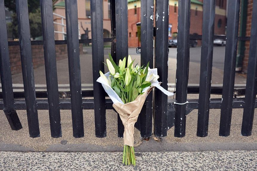 Flowers are left at the gate of Sydney Cricket Ground following the death of Australian batsman Phillip Hughes in Sydney on Nov 27, 2014. -- PHOTO: AFP