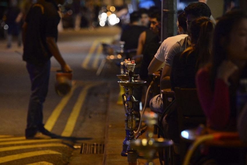 """A customer smokes a shisha or """"hookah"""" pipe at a cafe on Bussorah St on Nov 4, 2014.The importation, distribution and sale of shisha tobacco will be illegal in Singapore as of Friday. -- ST PHOTO: MARK CHEONG"""