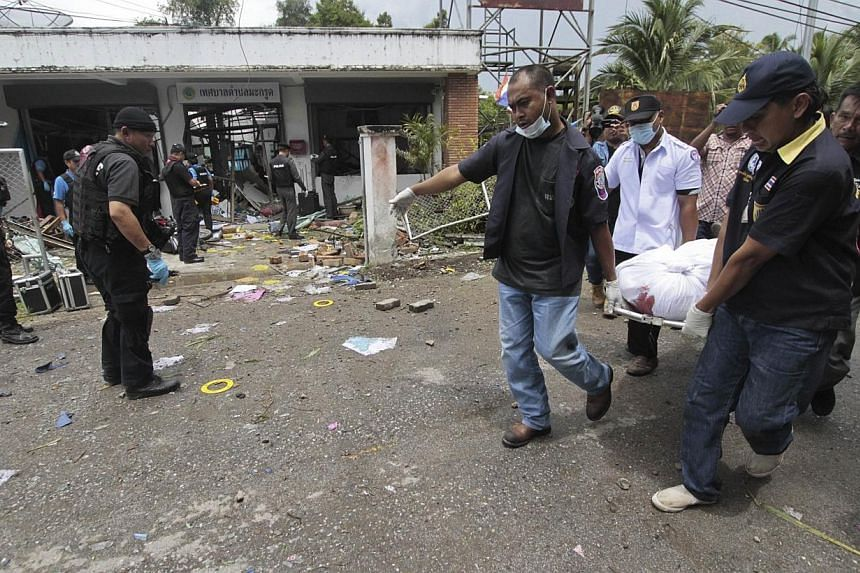 Rescue workers carry the body of shooting victim at the Kok Po district office to a hospital in Pattani province, south of Bangkok on Sept 11, 2014.A Thai court sentenced to death five suspected Muslim separatists convicted of killing four sold