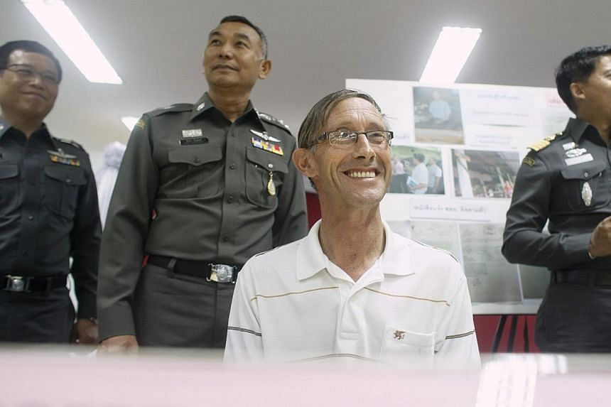 Robert David Hastings (centre), 61, from Britain, smiles during a news conference at the Immigration Detention Center in Bangkok on Nov 26, 2014. A British man wanted by British police for a string of paedophile offences has been arrested at a s