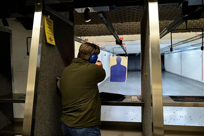 A retired police officer fires a gun at the Ultimate Defence Firing Range and Training Centre in St Peters, Missouri, some 32km west of Ferguson, on Nov 26, 2014. -- PHOTO: AFP