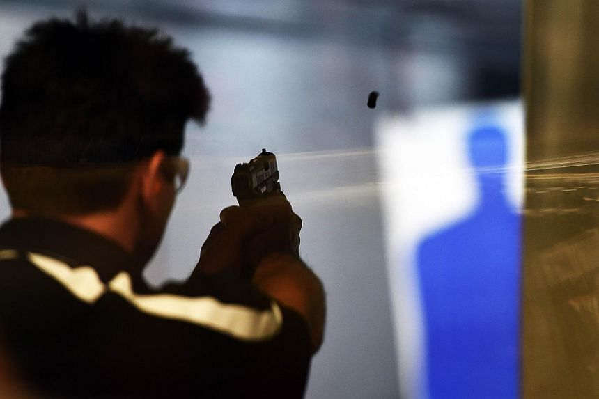 A man fires a handgun at the Ultimate Defence Firing Range and Training Centre in St Peters, Missouri, some 32km west of Ferguson, on Nov 26, 2014. -- PHOTO: AFP