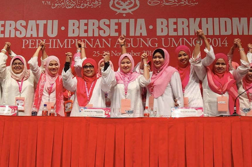 "Puteri Umno chief Mas Ermieyati Samsudin (fourth from left) with committee members during the Umno women's wing's general assembly on Nov 26, 2014. Puteri Umno has set up its own ""cyber commando"" unit in defence of the party, religion and race. -- PH"