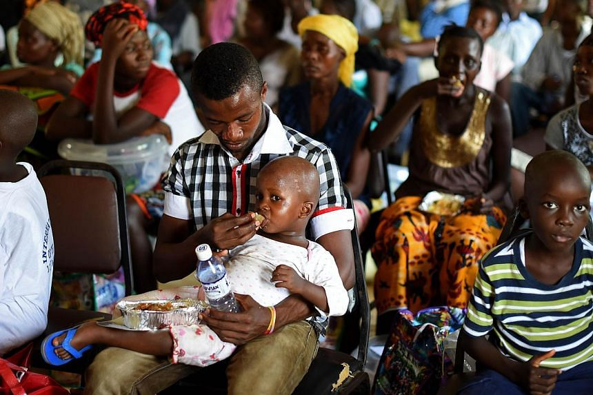 A child who survived the Ebola virus is fed by another survivor at a treatment centre in Sierra Leone on Nov 11, 2014.The death toll in the world's worst Ebola epidemic has risen to 5,689 out of 15,935 cases reported in eight countries by the e