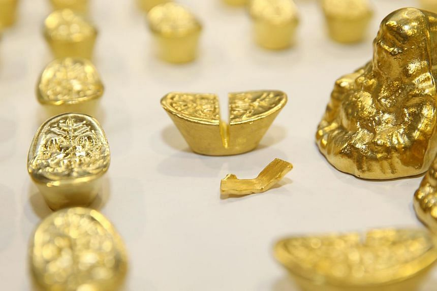 The fake gold ingots displayed by police at a press conference on Wed, Nov 26, 2014. -- ST PHOTO: SEAH KWANG PENG