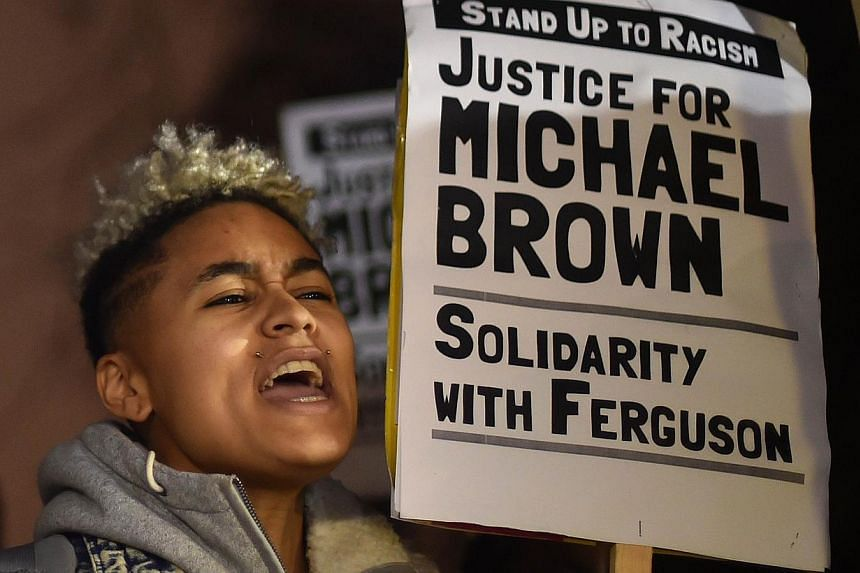 Demonstrators stand and chant with placards during a protest outside the US embassy in London on Nov 26, 2014 over the US court decision not to charge the policeman who killed unarmed black teenager Michael Brown in the town of Ferguson. -- PHOTO: &n