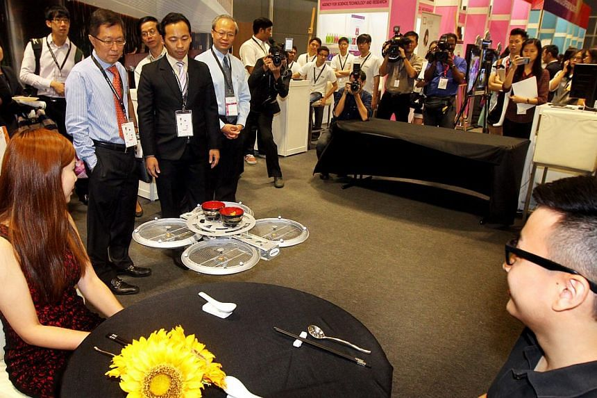 Visitors watching a flying robot waiter in action at the launch of National Productivity Month on Oct 7, 2014.-- PHOTO: LIANHE ZAOBAO