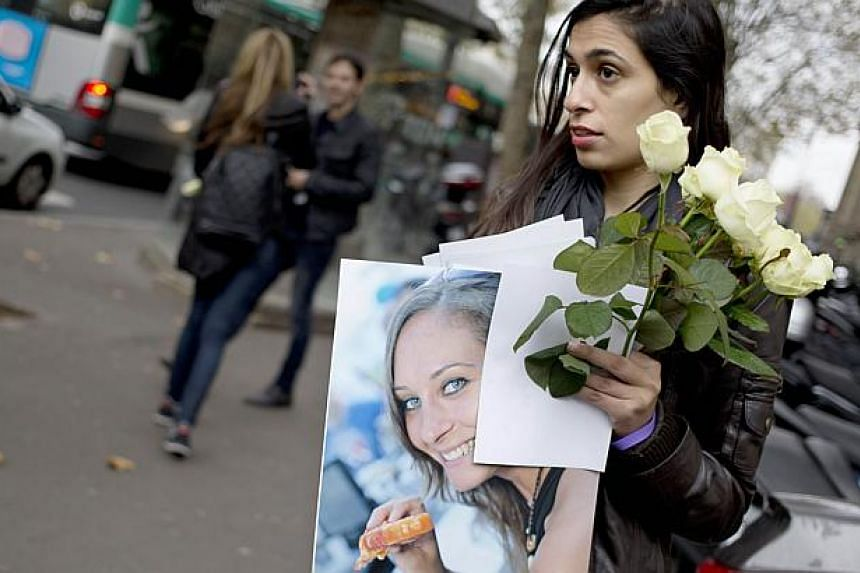 A woman holds a picture portrait of Lee Zitouni as friends and relatives stand in front of the Paris' court house, on Nov 27, 2014, during the trial of a French driver and passenger for a hit-and-run road accident in Tel Aviv that killed the young Is