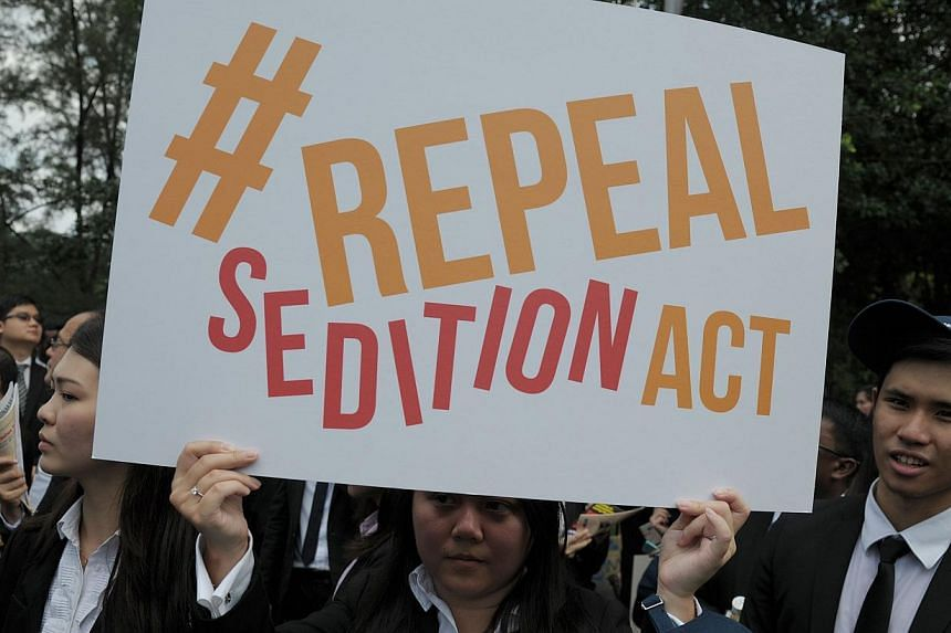In a photo taken on Oct 16, 2014, a Malaysian Lawyer holds a placard outside Parliament house during a rally to repeal the Sedition Act in Kuala Lumpur. -- PHOTO: AFP