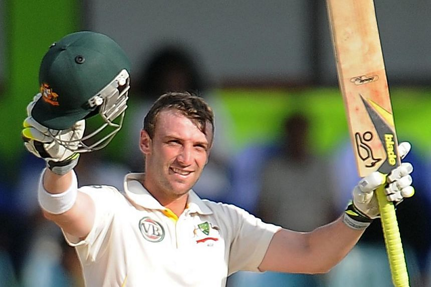 Australian batsman Phillip Hughes in a Sept 11, 2011, file picture raising his bat and helmet in celebration after scoring a century (100 runs) during the fourth day of the third and final Test match between Australia and Sri Lanka at The Sinhalese S