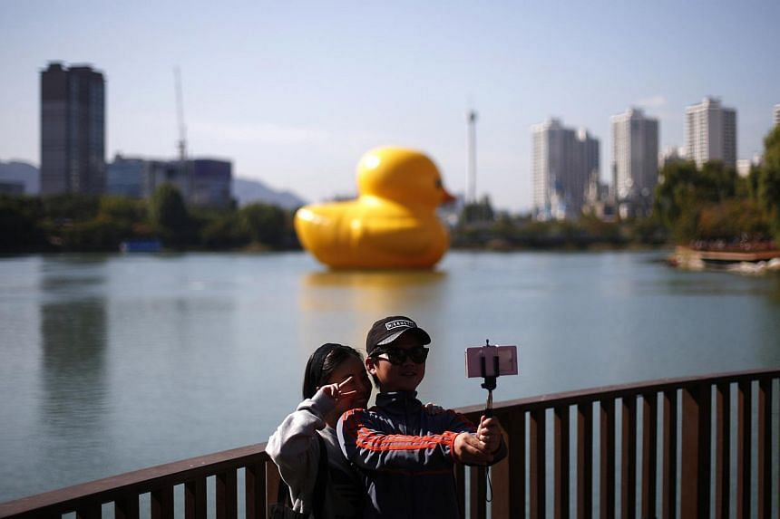 """A couple takes a """"selfie"""" in front of the giant inflatable Rubber Duck installation floating in Seokchon Lake in Seoul on Oct 14, 2014. -- PHOTO: REUTERS"""