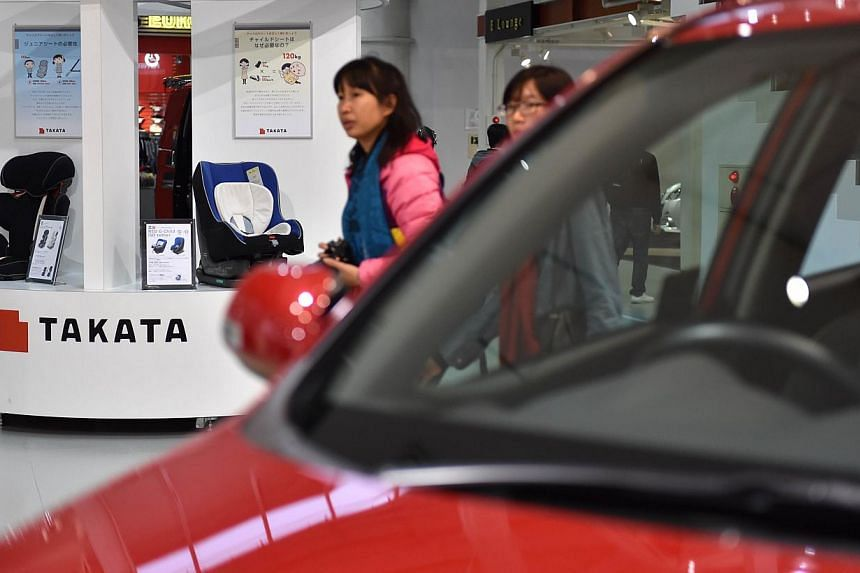 Visitors look at displays of Japanese auto parts maker Takata (left) at a car showroom in Tokyo on Nov 11, 2014. US regulators on Wednesday pressured Japanese auto parts maker Takata to expand its recall of potentially defective airbags across t