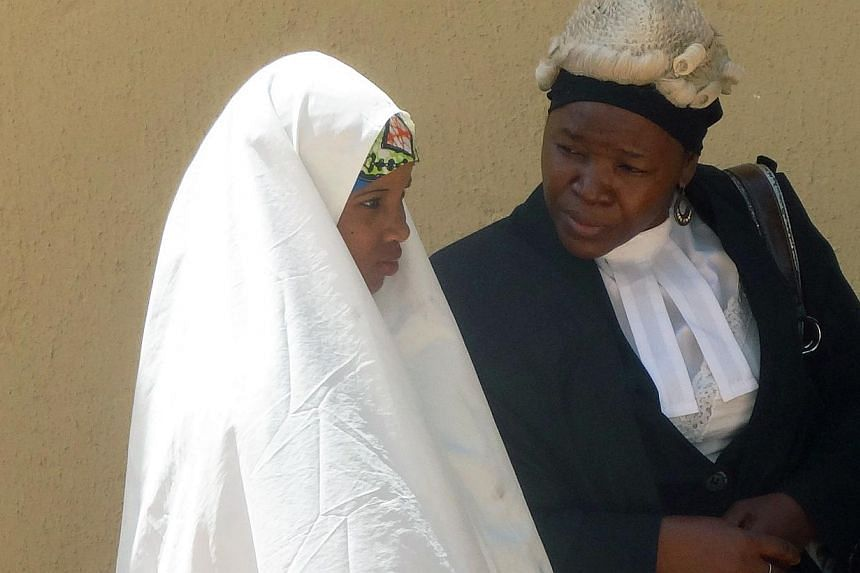 Wasila Tasi'u, 14, speaks with an unidentified defence counsel during a 30-minute break on the first day of her trial at Kano state high court in the village of Gezawa outside Kano on Oct 30, 2014. Tasi'u isaccused of murdering her 35-year-old