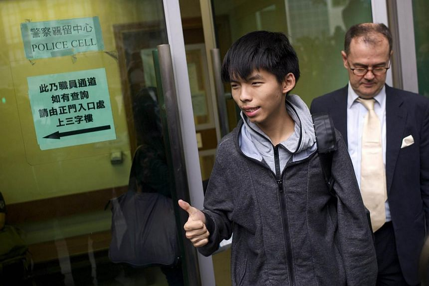 Student leader Joshua Wong (centre) gives a thumbs up as he exits a courthouse with his lawyer Michael Vidler after Wong was released on bail in Hong Kong on November 27, 2014. A court in the semi-autonomous city banned the pro-democracy leader from