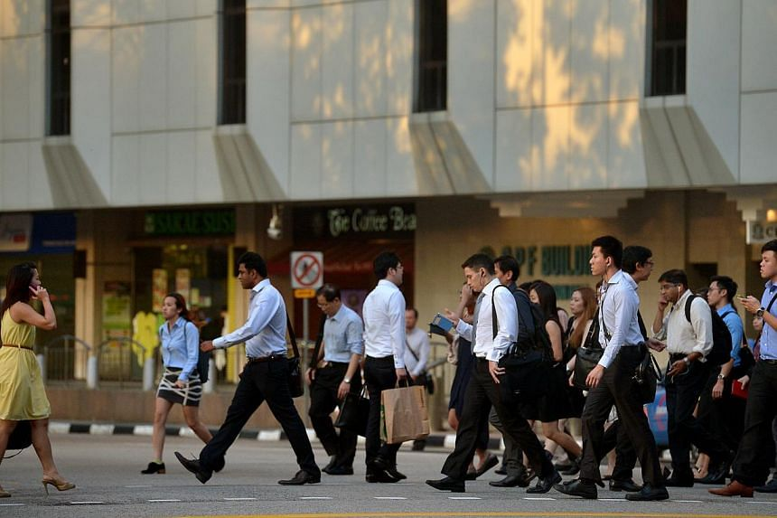 Office workers in the Central Business District. Real income growth slowed significantly this year, according to preliminary figures released on Friday by the Manpower Ministry. -- PHOTO: ST FILE