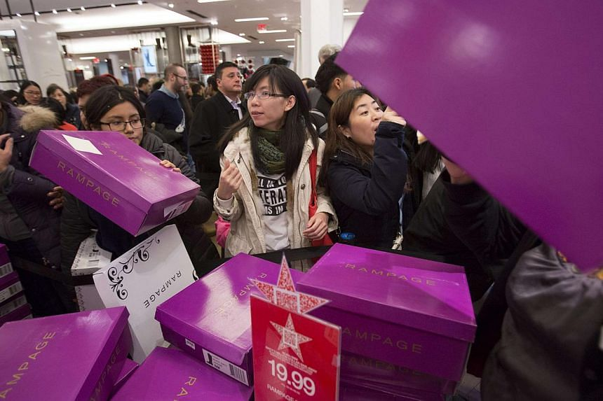 People sorting through boxes of shoes in Macy's in New York on Nov 27, 2014. Singaporeans can join in the shopping frenzy online as e-tailers cash in on the post-Thanksgiving tradition by offering deep discounts over the weekend. -- PHOTO: REUTERS
