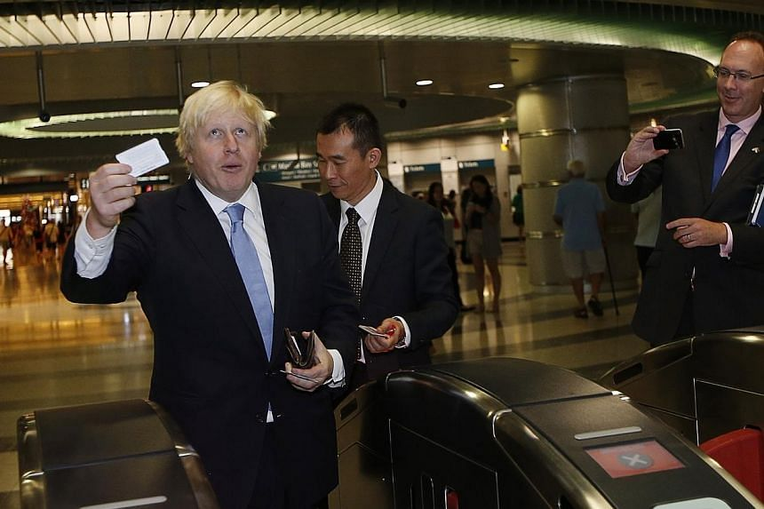 Mayor of London Boris Johnson taps his fare card as he takes a train with Managing Director of Singapore Mass Rapid Transit (SMRT) Trains Lee Ling Wee (centre) at Bayfront Station during his visit in Singapore on Nov 28, 2014. -- PHOTO: REUTERS