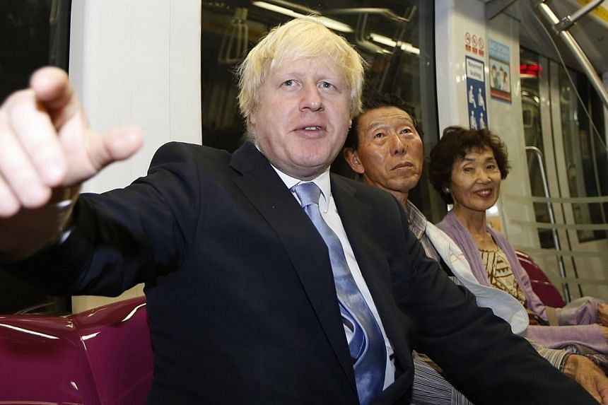 Mayor of London Boris Johnson sits next to two Japanese tourists on the train at Bayfront Mass Rapid Transit (MRT) station during his visit in Singapore on Nov 28, 2014. -- PHOTO: REUTERS
